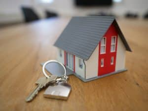 white and red wooden house miniature on brown table